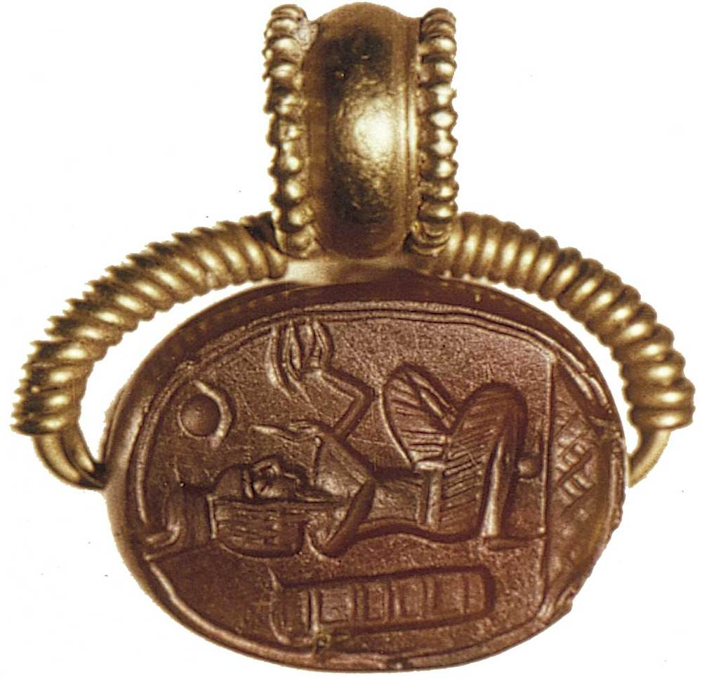 Època feniciopúnica. Escarabeu púnic de cornalina, amb muntura d´or per ser utilitzat com a penjoll; representa un motiu egipcitzant d´un faraó adorant l´ull d´Udjat d´Horus, amb un disc solar i un creixent llunar i, darrere el faraó, un cartutx amb signes jeroglífics; final del s. V aC.