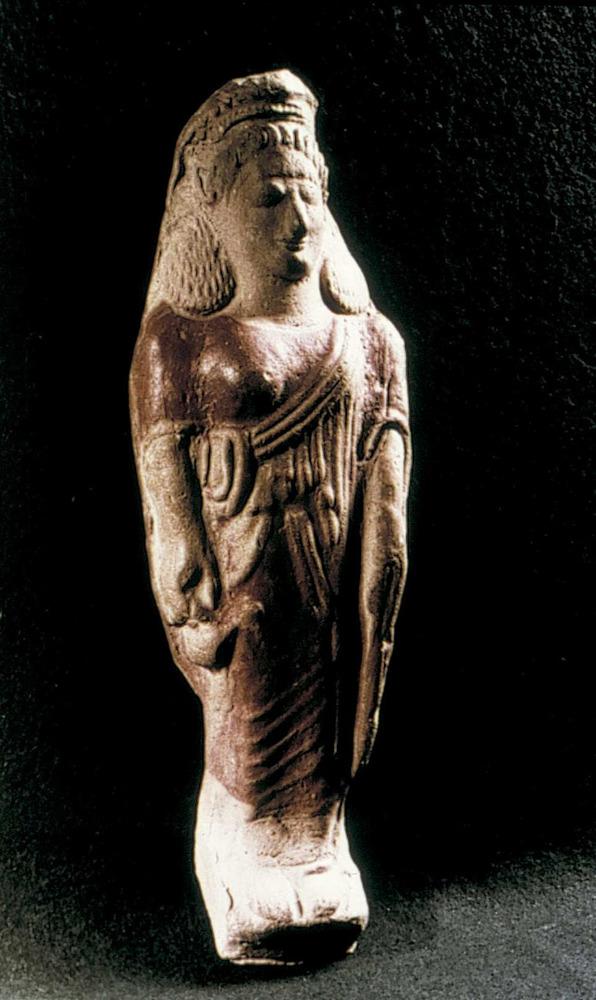 Època feniciopúnica. Figura femenina de terracota portant un colom, amb el vestit pintat de color vermell, que reprodueix un model grec arcaic de korai; final s. V aC.