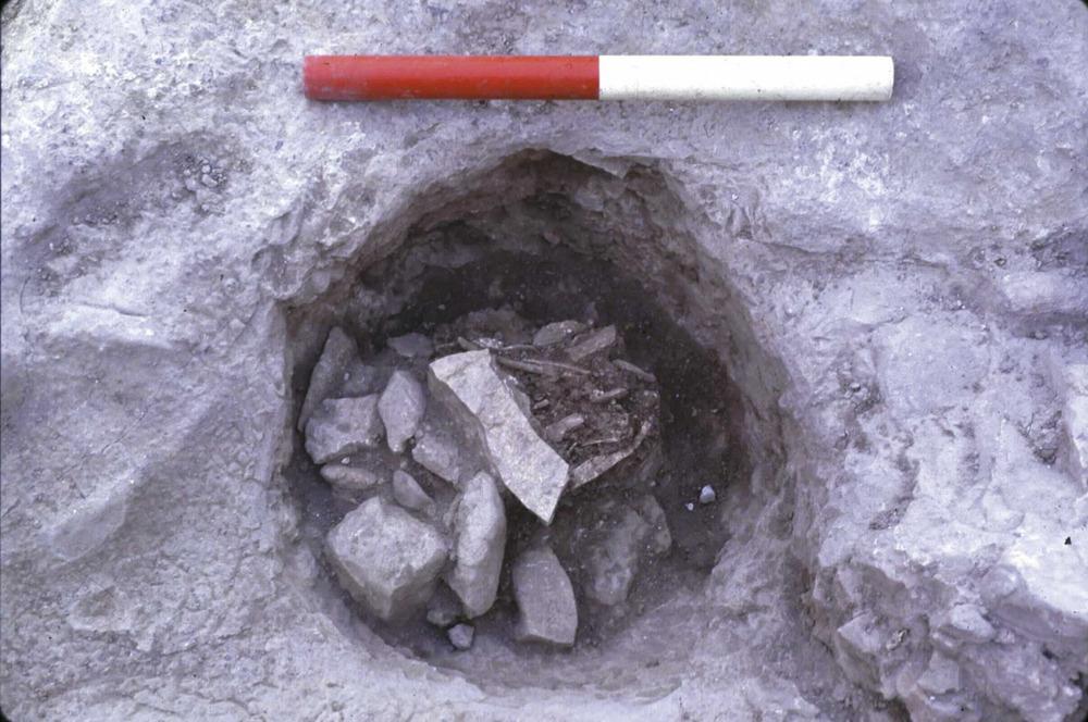 Època feniciopúnica. Enterrament fenici de cremació dipositat dins una cavitat circular tallada a la roca, contenint les restes d'un home d'uns 25 anys i d'una adolescent, excavat al Puig des Molins, al solar de can Partit, l'any 1985. Pertany al final del s. VII o a l'inici del VI aC. Foto: Benjamí Costa Ribas.