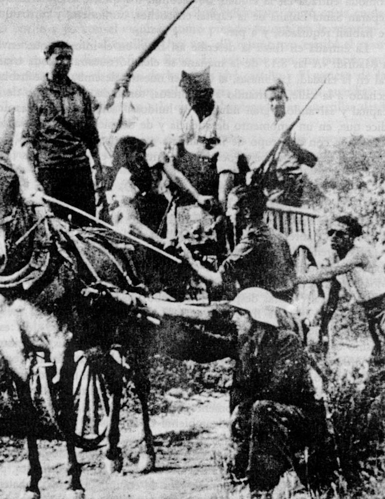 Un grup de milicians puja a un carro una ràdio de campanya, durant la Guerra Civil Espanyola.
