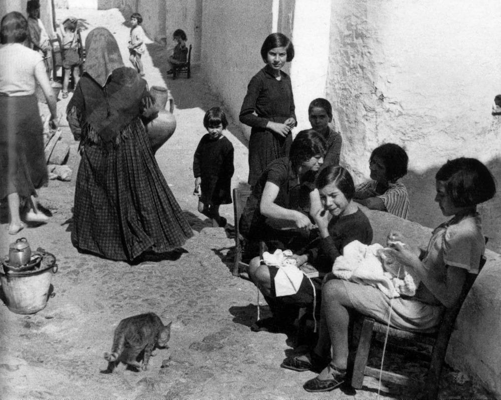 Tradicionalment, sa Penya ha estat un barri popular, de gent marinera i immigrants rurals, amb forta dinàmica demogràfica. El carrer, empedrat i entrespolat, era una prolongació natural de la casa gràcies al microclima confortable, afavorit per la disposició de la trama urbana. Bona part de la jornada, mentre els homes treballaven, dones i infants s'ensenyorien de la via pública, lloc de reunió social i àrea de treball femení,<br />majoritàriament labors de costura, bé per a ús personal o per encàrrec i a comissió. Foto: Emilio Orsinger. Extret d´<em>Eivissa. L´illa d´un temps</em>.