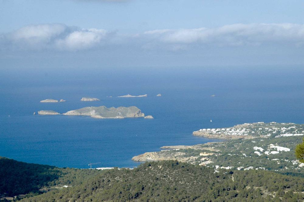 Sant Agustí des Vedrà. Una vista de la costa amb la urbanització del puig des Dofí i Comte, amb s´Espartar i ses Bledes al fons. Foto: Chus Adamuz.