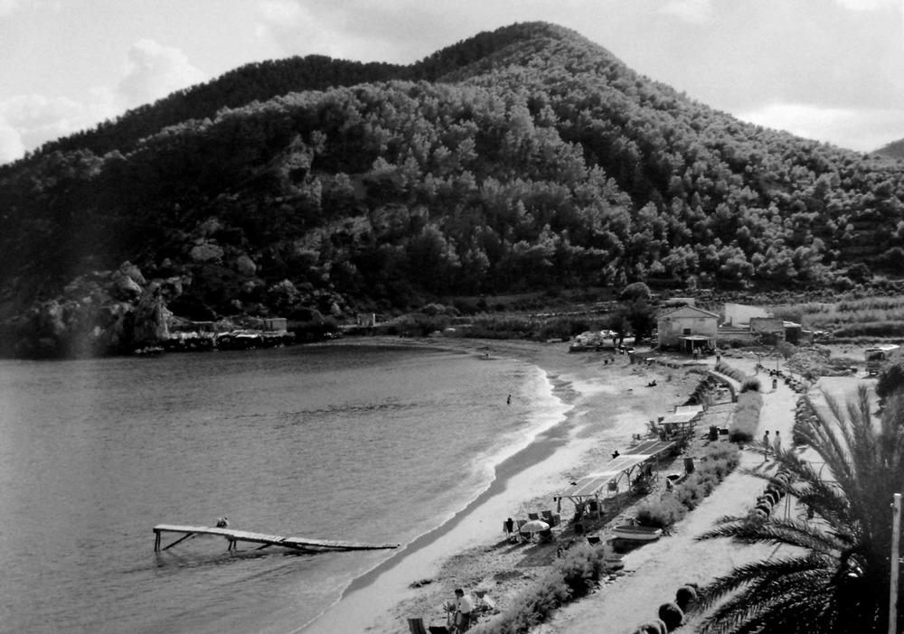 """Sant Vicent de sa Cala. Imatge del port de sa Cala de 1965. Es poden observar sa Casassa i el quiosc d´en Rota al seu costat; al fons, els antics varadors. Foto: cortesia de la família """"Rota""""."""