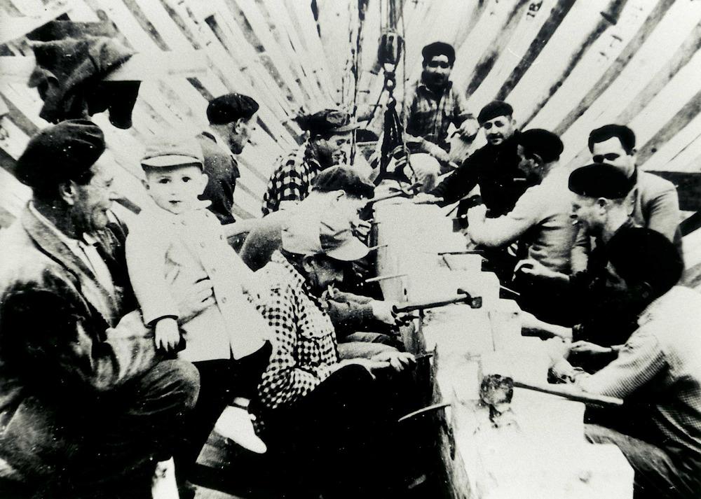 """Construcció Naval. Treballadors col·loquen la cussia a una embarcació; a l´esquerra el mestre d´aixa Joan Tur """"Guardiola""""."""