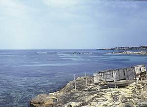A la dreta de la imatge es veu l´illa de s´Aigua Dolça des des Pujols, a Formentera. Al seu davant es poden veure les crestes i els crestalls, recoberts d´escuma. Foto: Enric Ribes i Marí.