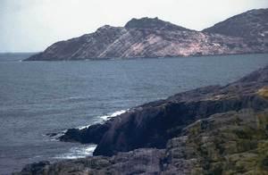 Geologia. Un exemple del triàsic muschelkalk (Tm), a la punta d´en Valls; al fons, Tagomago. Foto: Xavier Guasch Ribas.