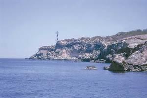 En primer terme, el tram de la costa de Sant Joan de Labritja conegut com es Grill Ferro; al fons, el far des Moscarter. Foto: Alberto Tostón Calle.