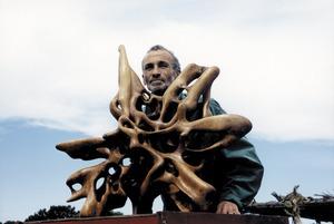 Dicky Medow amb una estàtua de fusta.