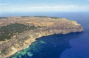Costa espadada de la Mola, a la zona de cala Codolar, la punta de sa Ruda i, al fons, el far de Formentera. Foto Pins.