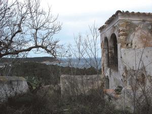 Can Lluquí de sa Cova, una de les hisendes més antigues de la vénda des Niu des Corbs, amb la punta de Xarraca, al fons. Foto: Josep Antoni Prats Serra.