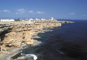 La punta Prima des de cala en Baster, típica costa de penya-segat, amb la torre de Punta Prima al seu extrem. Foto: David García Jiménez.