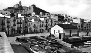 Sa Riba va mantenir llargament el secular esperit mariner que mostra aquesta imatge de l'acabament dels anys vint del segle passat. En primer pla, llaüts, xalanes i xarxes de pesca, i a la dreta, el pòsit de pescadors i uns petits magatzems per guardar-hi els estris. Al fons, dominades per l'imponent baluard de Santa Llúcia, les cases s'arrengleren mostrant la disposició de la primitiva línia de costa, en un temps vorejada pel camí de la Torre de Mar, guardiana del port.