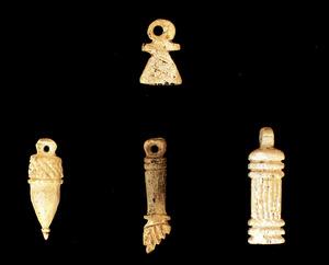 Art. Amulets d´època púnica. Per aquest ordre, signe de Tanit, aglà, mà dreta amb el puny tancat i fent la figa, i ara. Foto: cortesia del Museu Arqueològic d´Eivissa.