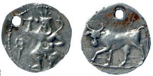 Moneda de plata de la seca ebusitana, encunyada durant la Segona Guerra Púnica, amb el déu Bes amb una serp i una maça i el revers amb el toro en posició d´avançar o de cotar. Foto: Museu Arqueològic d´Eivissa i Formentera.