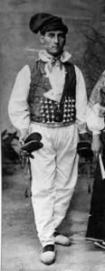 Home amb el vestit blanc format per calçons d´aquest color, jupetí de color i barretina. Foto: Narcís Puget.